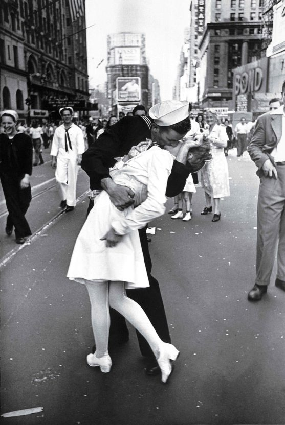 A jubilant American sailor clutching a white-uniformed nurse in a back-bending, passionate kiss as he vents his joy while thousands jam Times Square to celebrate the long awaited-victory over Japan.